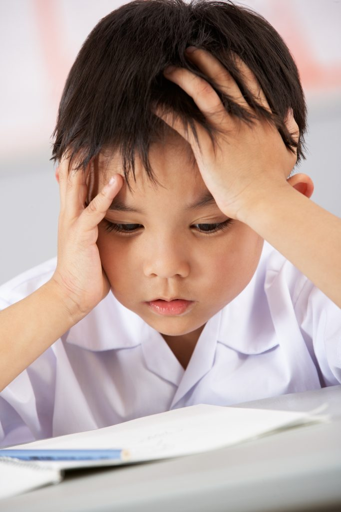 Unhappy Male Student Working At Desk In Chinese School Classroom; child has difficulty learning the alphabet