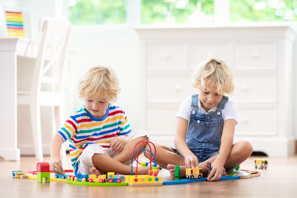 Kids play with wooden railway. Child with toy train. Intentional play for young children. Little boy building railroad tracks on white floor at home or kindergarten. Cute kid playing cars and engine.