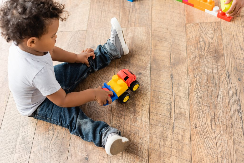 Toddler boy playing with toy truck for intentional play session