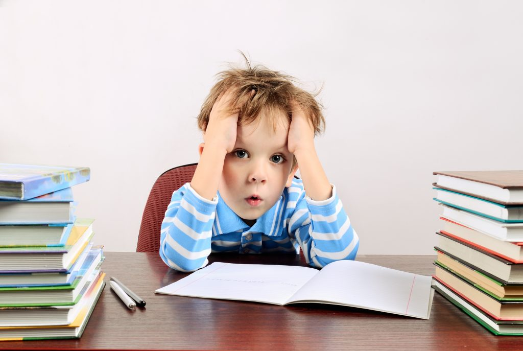 little tired boy sitting at a desk horizontal; child has difficulty learning the alphabet