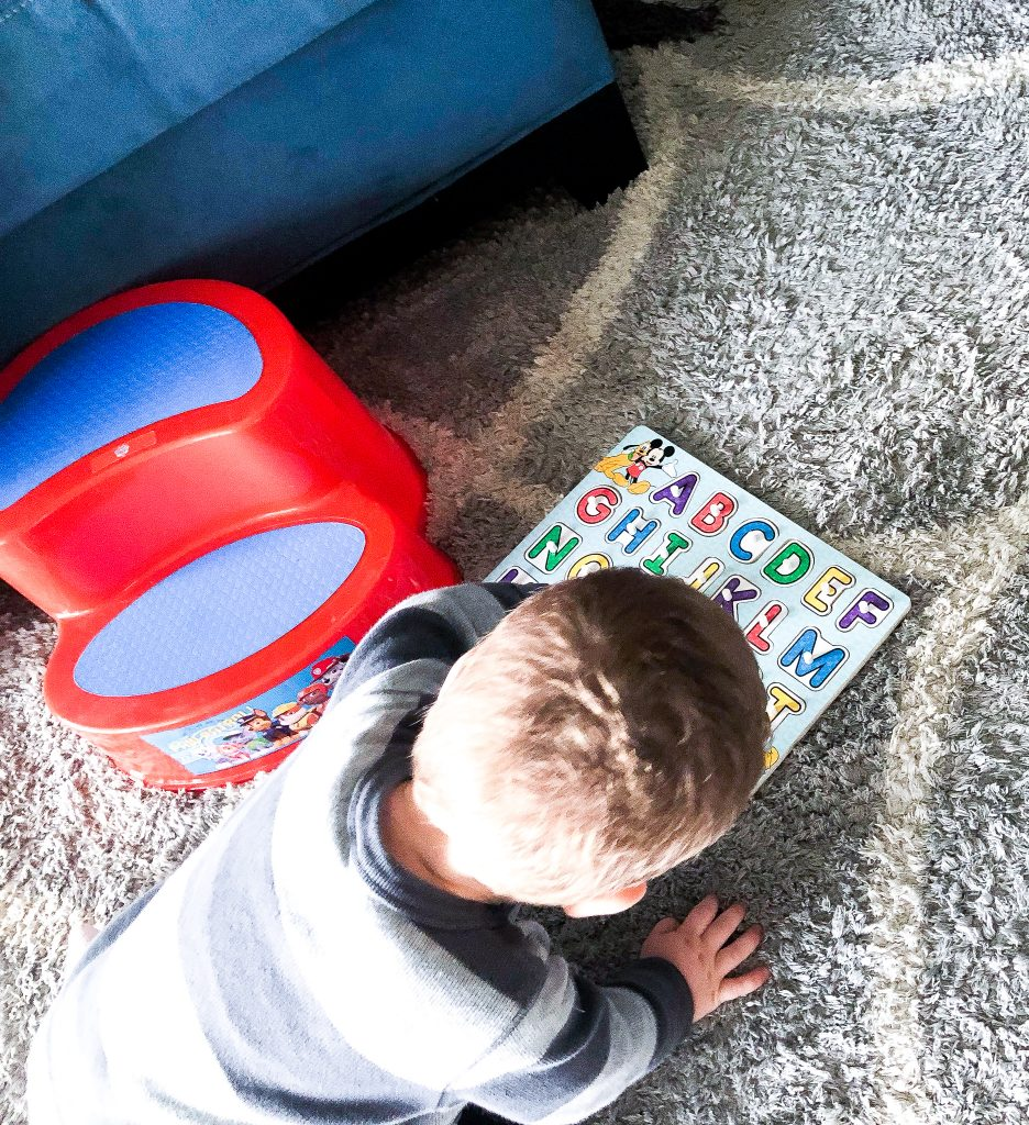 Young boy playing with alphabet puzzle; child has difficulty learning the alphabet