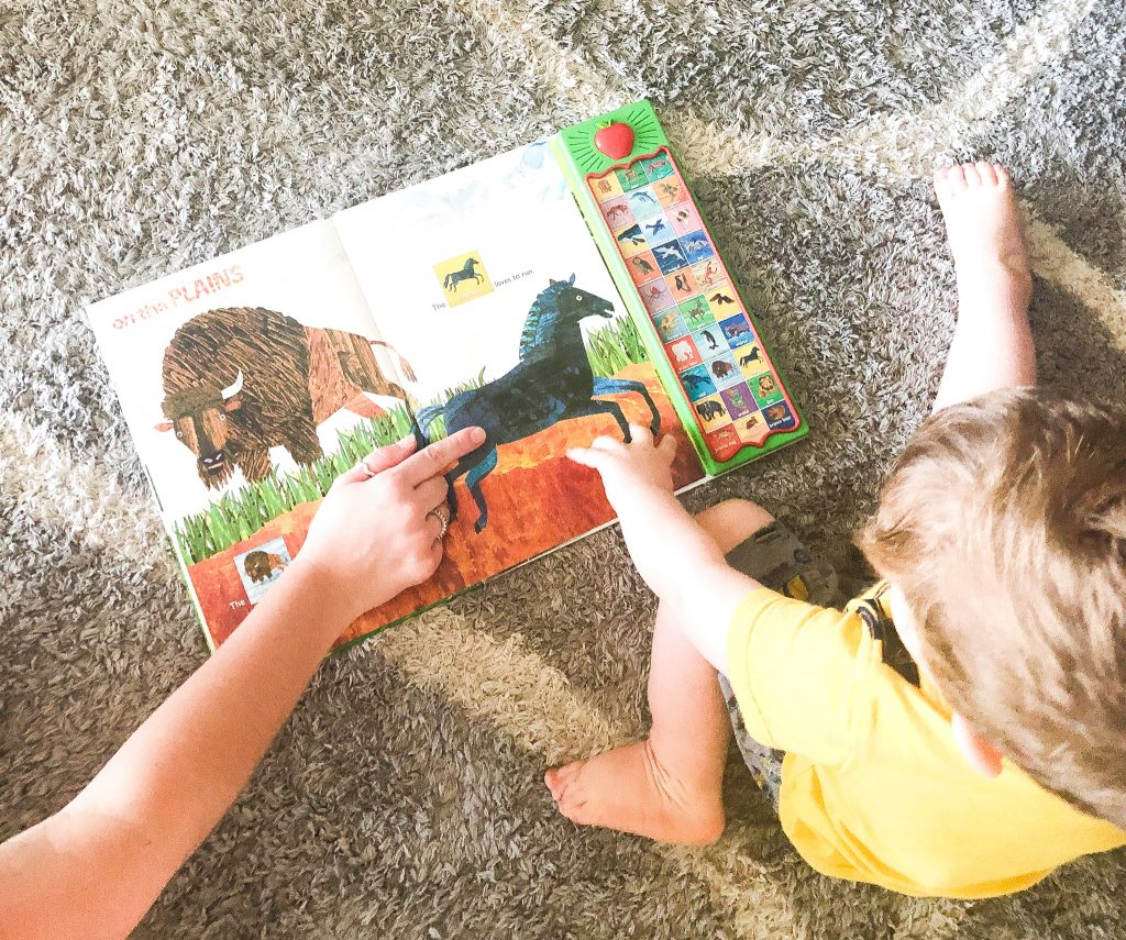 Little boy looking at a sound book with animals to support print motivation