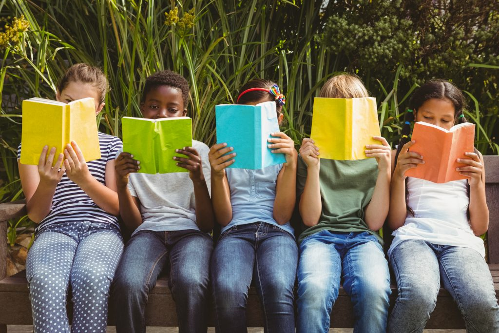 Children with high print motivation sitting in row and reading books at the park